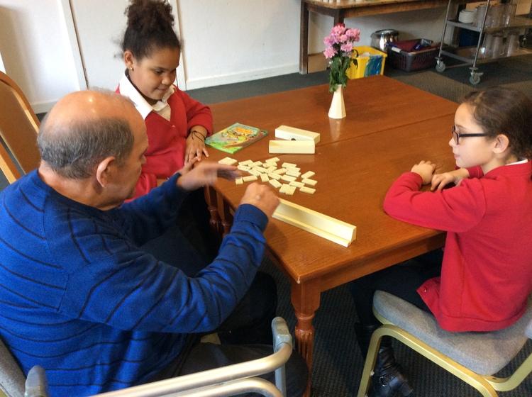 Three playing dominoes
